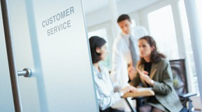 Businessman and two businesswomen discussing in customer service office